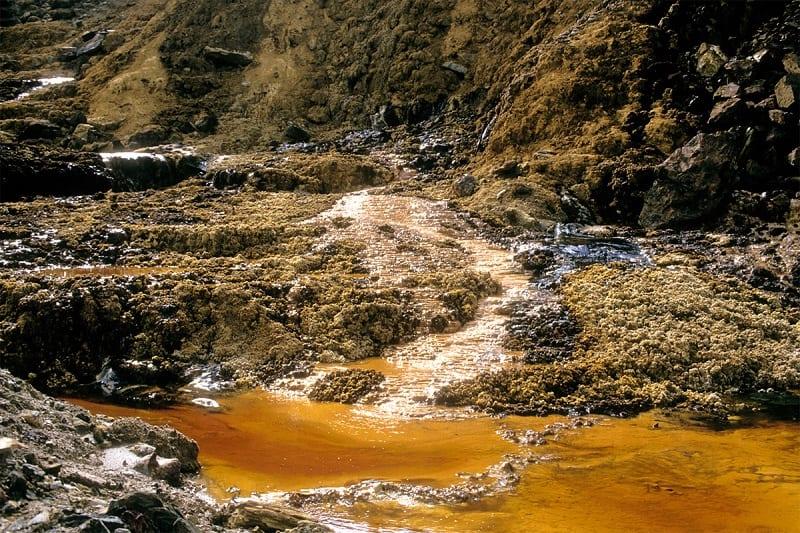 Khu vực đất bị ô nhiễm nặng, bị xói mòn và nước đổi sang màu vàng cam