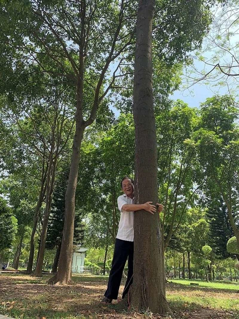một bác trai cười tươi vòng tay ôm quanh gốc cây sao đen to lớn
